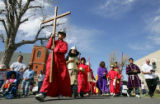 Eric Haro (cq), 10, of Denver, dressed as a Roman, carries the cross as about 40 parishioners of...