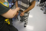 A prisoner with an ICE hold, who wishes to remain unidentified, has his hand-cuffs removed as he...