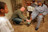 Sgt. Leroy Scott, CQ, right, has his leg examined by his neighbor Falcon home on February 20,...