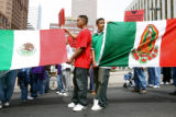 Luis Villagran (cq) (in red shirt) and Abraham Ramirez (cq) march with the Mexican and Virgin of...