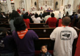 Victor Cruz (cq), 4, looks up at his brother Javier during mass at the Cathedral of the Immaculate...