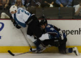 (DENVER, CO - 5/4/04) -- Colorado Avalanche defenseman Adam Foote, right,  ties up San Jose Sharks...