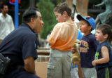 (7/15/2004 Denver) Denver Police Sergeant Johnny Martinez greets Evan Sanchez, 5, Nicolas...