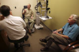 Dr. Randy Craven, (cq), left, listens to Peter Russell, before the exam, as Stephen Crout, right,...
