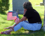A woman finds a shady spot at the cemetary were the remains of Chris Sitton was laid to rest while...