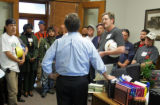 Denver City Attorney Cole Finegan, cq, center, talks to a group of construction workers gathered...