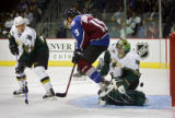 The Colorado Avalanche's Andrew Brunette (#15/LW) jumps to avoid a slapshot by teammate Joe Sakic...