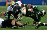 Colorado State Rams wide reciever Jonny Walker gets pulled down by University of Colorado...