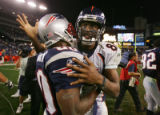 The Denver Broncos Javon Walker (#84, WR) hugs the New England Patriots' Troy Brown (#80, WR) at...