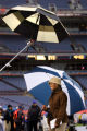 ESPN reporter Lisa Salters gets double coverage from a pair of umbrellas as she files a pre-game...