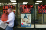 A man walks past Cash Payday Express on Stout Street in Downtown Denver on Monday, September 25,...