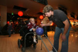 Colorado Avalanche hockey player John-Michael Liles, cq, helps Jake Sensenbaugh, 9, bowl at Lucky...