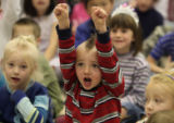 Daigen Menz (cq) ,age 5, raises his hands while Paul Sandos (cq), principle at Deer Creek...