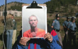 A member of the local media holds up a photo of 54 year old Duane Morrison across from the Platte...