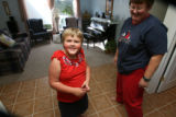 Tara,7, smiles after dancing with mom, Robin, in the area widened and tile floor installed for...