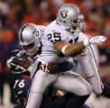 (RMN584) - Denver Broncos Kenard Lang, #76, drags down Oakland Raiders Justin Fargas, #25, in the...