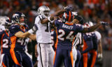The Denver Broncos' John Lynch (#47, S) pulls at the Oakland Raiders' Randy Moss (#18, WR) away...