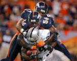 The Denver Broncos' Al Wilson (#56, LB) and Demetrin Veal (#97, DT) combine on the tackle of the...