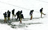 Members of the Evergreen football team clear snow off part of the field at Evergreen High school...