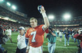 (DENVER, COLO., OCTOBER 16, 1995) Broncos quarterback John Elway holds his hat up to the crowd in...