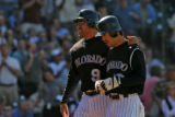 Colorado Rockies Vinny Castilla, left, heads to the dug-out with Kazuo Matsui after they both...