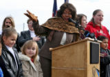 Mary Wilson, former singer with The Supremes, behind the podium, sings the National Anthem, with...