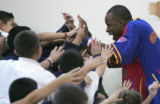 Harlem Globetrotter Herb Evans, gets high five from students  at  Pinnacle Charter School Thursday...