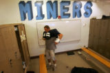 Danny Sprague, a 23-year-old senior at the Colorado School of Mines, puts on his pads before...