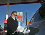 Nancy Owen (cq), of Lakewood, fills up her car with unleaded gas, $1.99 per gallon, Wednesday...