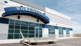 (DENVER, Colo.,  May 11, 2004) An empty air cargo cart sits in front of a WorldPort building at...