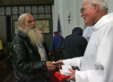 Leerie Tagney (cq), left says thank you to Father Kennedy, right, after receiving a $20 gift at...