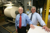 left to right, Frank Dixon, (cq), Senior Vice-President of Operations, stands before new presses...