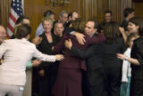 Speaker of the House Nancy Pelosi gives Rep. Ed Perlmutter, D-Colo., a hug after conducting his...