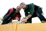 Master timber framers Uwe Schreple, left, and Helmut Elbs, from Germany, secure a beam in place...