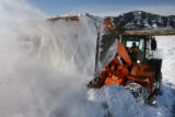 MJM161 Snow blows as  a CDOT front loader clears snow drifts across highway 93 as high winds...