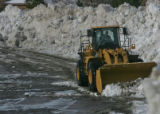 A Caterpillar frontend loader is used to make a wall of snow around the parking lot at James A....