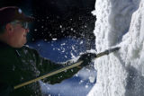 Team Idaho snow sculptor Bill Dow (cq), of Billings, Mont. chips away at a huge block of snow at...