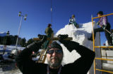 Team Canada snow sculptor Ron Pearce (cq) of Ontario uses a wire saw to cut off a large chunk of...