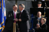 Outgoing Colorado Governor Bill Owens, left, shakes hands with incoming Governor Bill Ritter at...