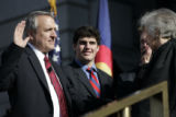 Colorado Governor Bill Ritter (l) takes the oath of office with the honorable Mary Mullarkey (r),...