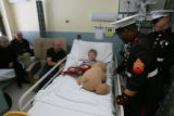 Ben Miller, 6, (cq), sits in his bed with family and soldiers...left to right, Marie and Donald...
