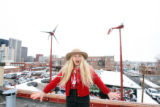 Marilyn Megenity, (cq), on the roof with her windmills and her solar panels recently installed on...