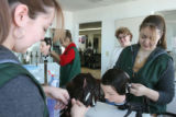 Stella Padilla, (cq), center with glasses, supervises two Cosmetology Degree students, left,...