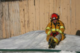 (DLM7948) -   An exhausted firefighter rests on a bank of snow after fighting a fire at the Castle...