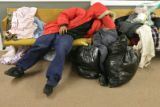 (DLM8342) -  J. Bradford sleeps amongst the piles of donated warm clothes and blankets he and...