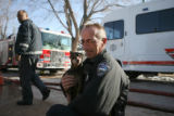 Colorado Spring Police officer, Sheldon Schnese, cq, holds a miniature pintcher, in his arms,...