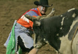 Professional bull fighter Lance Brittan of Windsor, Colo., steps in the path of a bull after the...