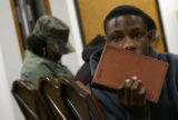 A young man sits with a bible in hand at a youth bible study at Rising Star Missionary Baptist...