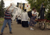(DENVER, Colo., Aug 6, 2004) Nicholas Tam,10, left in stripes and jeans, puts a plastic poncho...