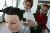 Stella Padilla, (cq), left with glasses, right of mannequin head, instructs Flora Flores, (cq),...